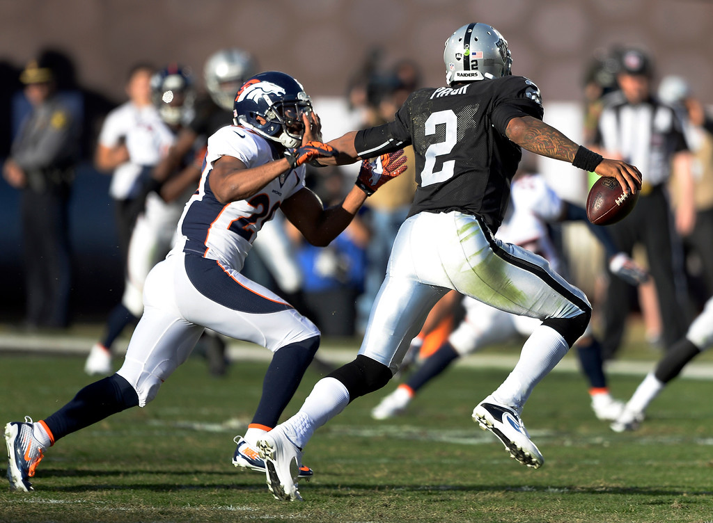 . Oakland Raiders quarterback Terrelle Pryor (2) stiff arms Denver Broncos free safety Michael Huff (29) as he scrambles out of the pocket during the third quarter at O.co Coliseum. (Photo by John Leyba/The Denver Post)