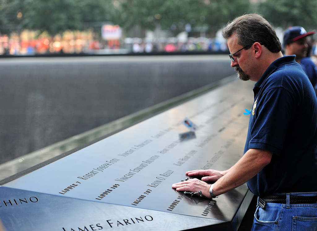 . Drew Taylor pauses near the name of a New York City Fire Department firefighter at the South Tower reflecting pool of the 9/11 Memorial during ceremonies for the twelfth anniversary of the terrorist attacks on lower Manhattan at the World Trade Center site on September 11, 2013 in New York City.  (Photo by Stan Honda-Pool/Getty Images)