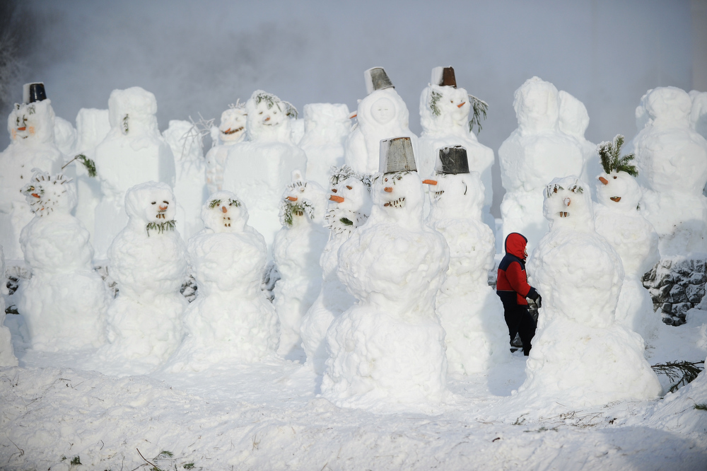 Description of . A child walks amidst the numerous snowmen built in a park in  central Moscow, on December 29, 2011. New Year's is the biggest holiday of the year in Russia, and is followed by the Orthodox Christmas on January 7. AFP PHOTO / NATALIA KOLESNIKOVA
