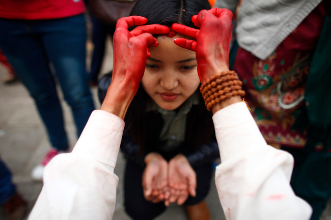 . A priest applies tilak or vermilion powder mixed with rice, on a girl\'s forehead outside a Hindu temple meant for Goddess Saraswati to mark Saraswati puja festival, in Katmandu, Nepal, Friday, Feb. 15, 2013. Saraswati Puja, is a special day for students when they show their respect to Saraswati, the goddess of knowledge and learning. Children are given their first writing and reading lessons during this festival. (AP Photo/Niranjan Shrestha)
