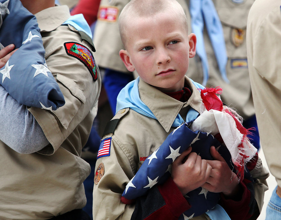 . Jeremy Rivers of Boy Scout Troop 13 from St. Mary\'s Catholic Church holds a tattered American flag Monday, May 27, 2013, during a Memorial Day flag retirement ceremony at Sugarloaf Assisted Living in Winona, Minn. The troop retired nine American flags from the community by burning them in a ceremonial fire and later burying the ashes. (AP Photo/Winona Daily News, Andrew Link)