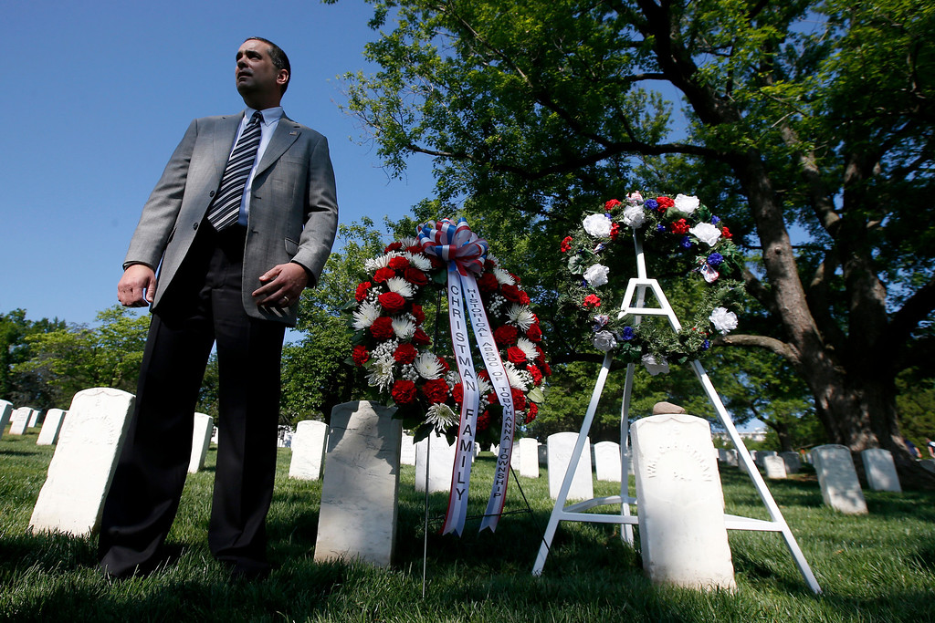. James Christman, from Allentown, Pa., great-grand nephew of Army Pvt. William Christman, who was the first military burial at the cemetery, stands by his grave after wreaths were laid marking the beginning of commemorations of the 150th anniversary of Arlington National Cemetery in Arlington, Va., Tuesday, May 13, 2014.  (AP Photo)