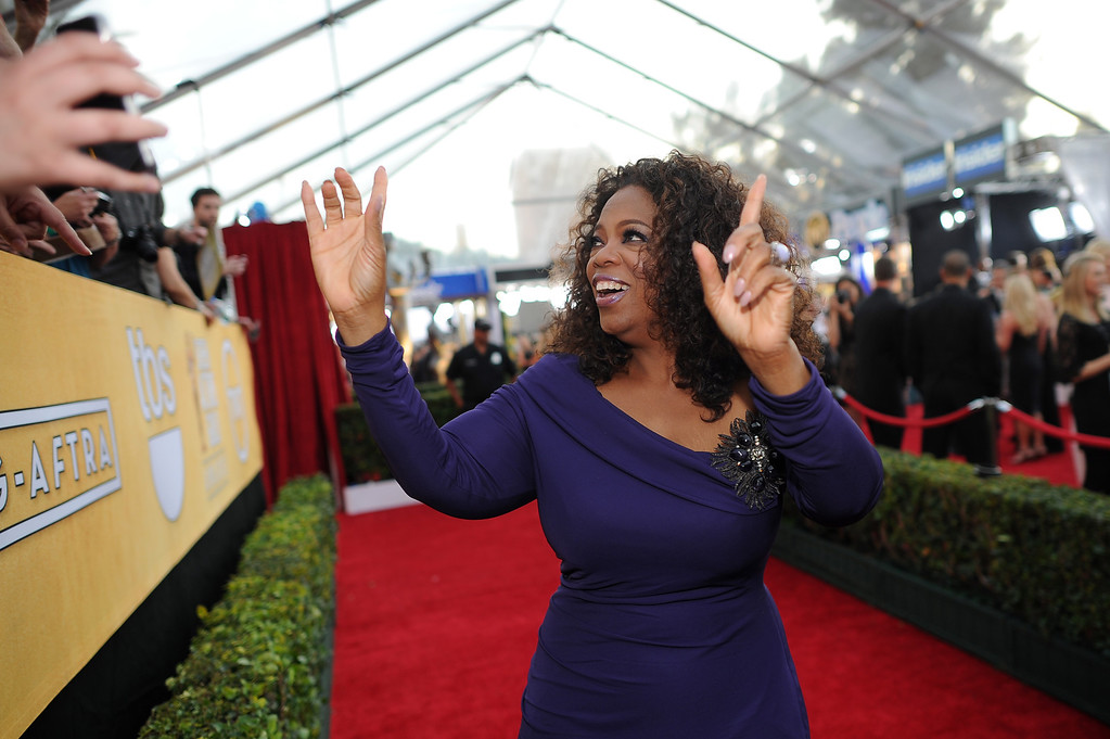 . Oprah Winfrey says hello to fans on the red carpet at the 20th Annual Screen Actors Guild Awards  at the Shrine Auditorium in Los Angeles, California on Saturday January 18, 2014 (Photo by Hans Gutknecht / Los Angeles Daily News)