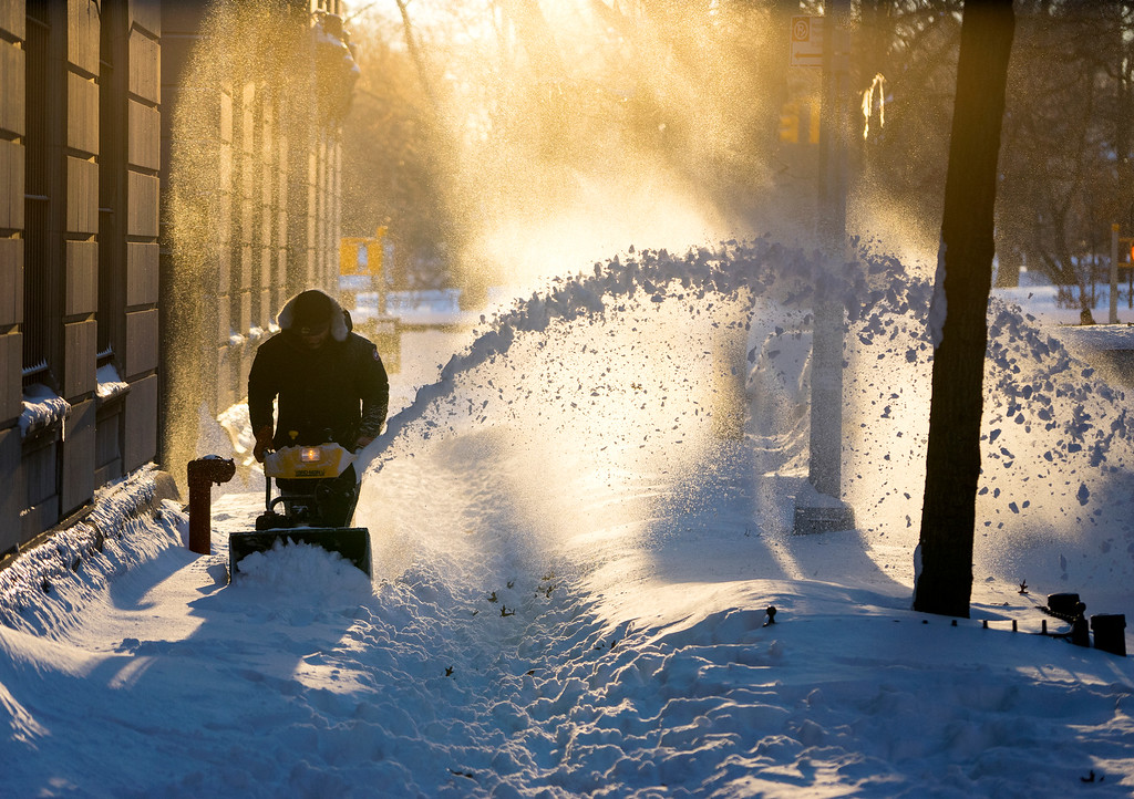 . Snow is cleared along a street in the Upper West Side neighborhood of New York Sunday, Jan. 24, 2016, in the wake of a storm that dumped heavy snow along the East Coast. (AP Photo/Craig Ruttle)