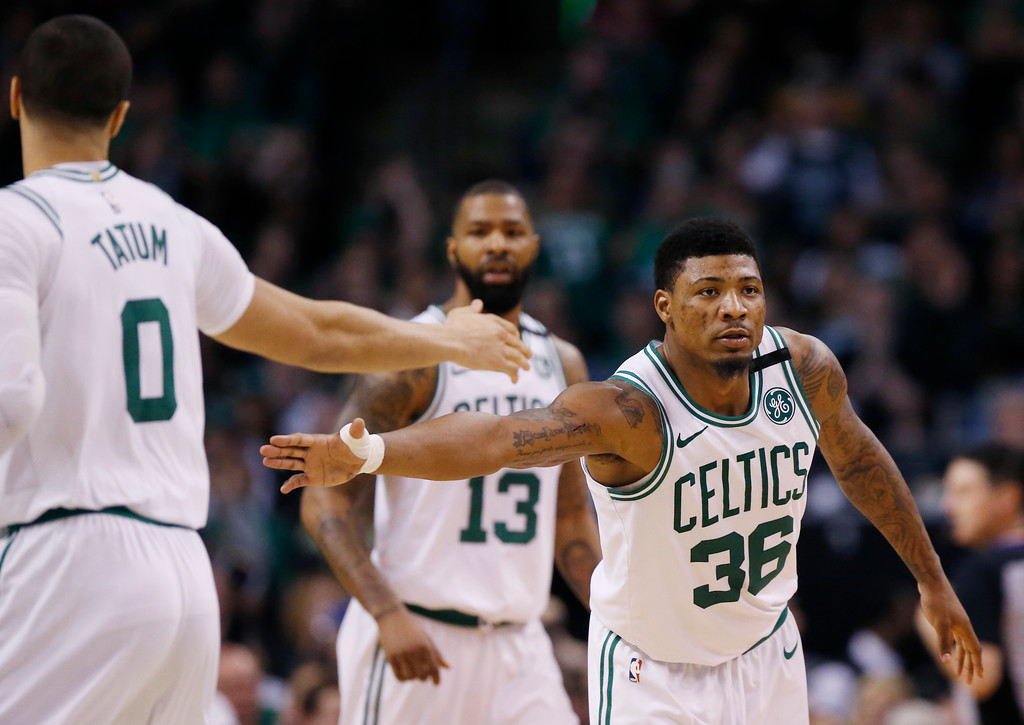 . Boston Celtics guard Marcus Smart (36) reaches to slap hands with forward Jayson Tatum (0) during the second half of Game 1 of the NBA basketball Eastern Conference Finals against the Cleveland Cavaliers, Sunday, May 13, 2018, in Boston. (AP Photo/Michael Dwyer)