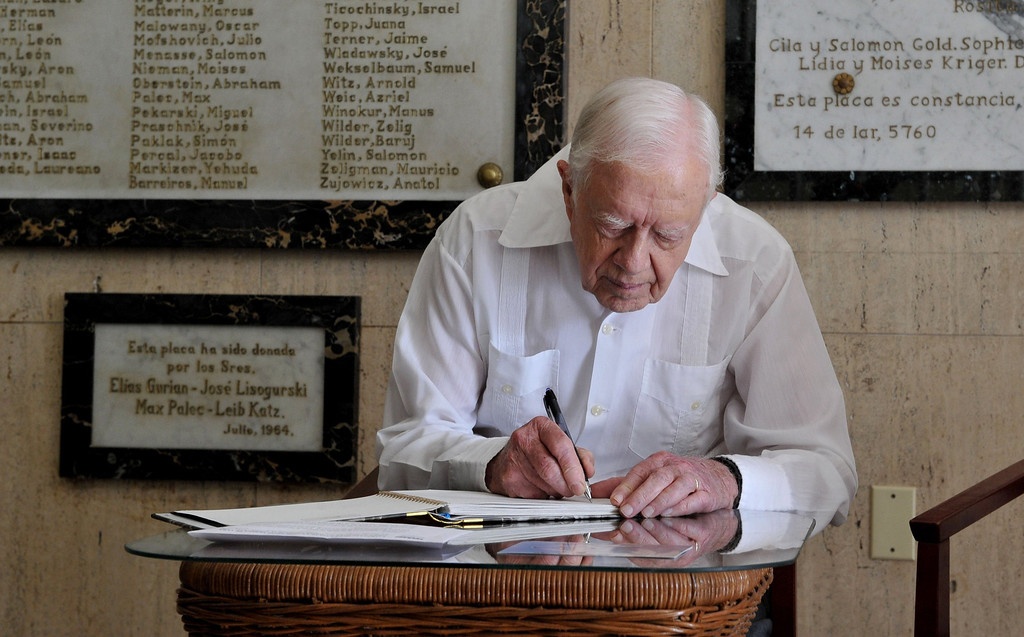 . Former President Jimmy Carter signs his name in the guest book at the Jewish Community center in Havana, Cuba, Monday March 28, 2011. Carter arrived in Cuba to discuss economic policies and ways to improve Washington-Havana relations, which are even more tense than usual over the imprisonment of Alan Gross, a U.S. contractor, on the island. C  (AP Photo/Adalberto Roque, Pool)