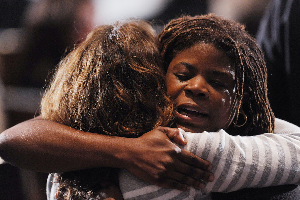 . NEWTOWN, CT - DECEMBER 16:  Mourners comfort one another before U.S. President Barack Obama speaks at an interfaith vigil for the shooting victims from Sandy Hook Elementary School on December 16, 2012 at Newtown High School in Newtown, Connecticut. Twenty-six people were shot dead, including twenty children, after a gunman identified as Adam Lanza opened fire at Sandy Hook Elementary School. Lanza also reportedly had committed suicide at the scene. A 28th person, believed to be Nancy Lanza, found dead in a house in town, was also believed to have been shot by Adam Lanza. (Photo by Olivier Douliery-Pool/Getty Images)