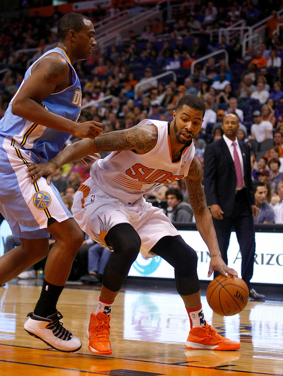 . Phoenix Suns power forward Marcus Morris (15), right, drives on Denver Nuggets power forward Darrell Arthur (00) in the third quarter during an NBA basketball game on Friday, Nov. 8, 2013, in Phoenix. The Suns defeated the Nuggets 114-93. (AP Photo/Rick Scuteri)
