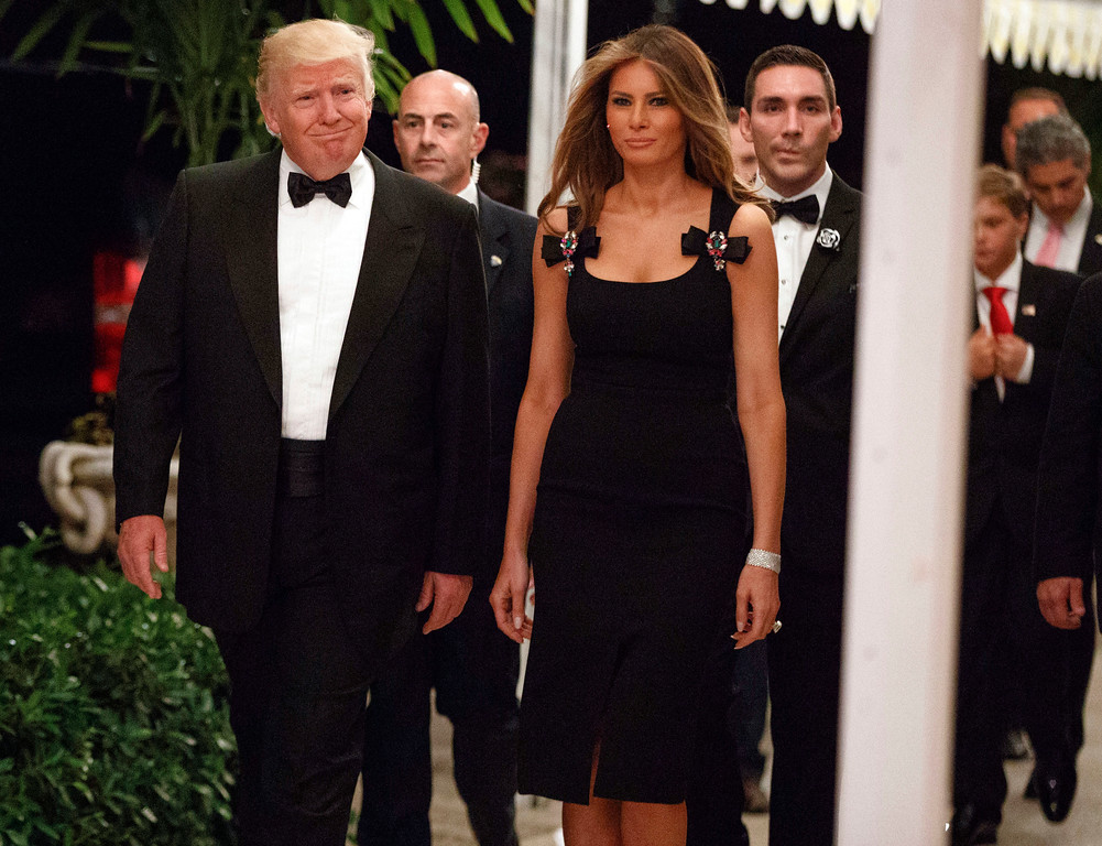 . FILe - This Dec. 31, 2016 file photo shows President-elect Donald Trump, left, and his wife Melania Trump arriving for a New Year\'s Eve party at Mar-a-Lago in Palm Beach, Fla.  Throughout the bruising presidential race, Mrs. Trump kept her look to typical wealthy socialite. Her blouses were often jewel toned, her dresses and jumpsuits from European designers that include Gucci and Roland Mouret, but Americans, too.(AP Photo/Evan Vucci, File)