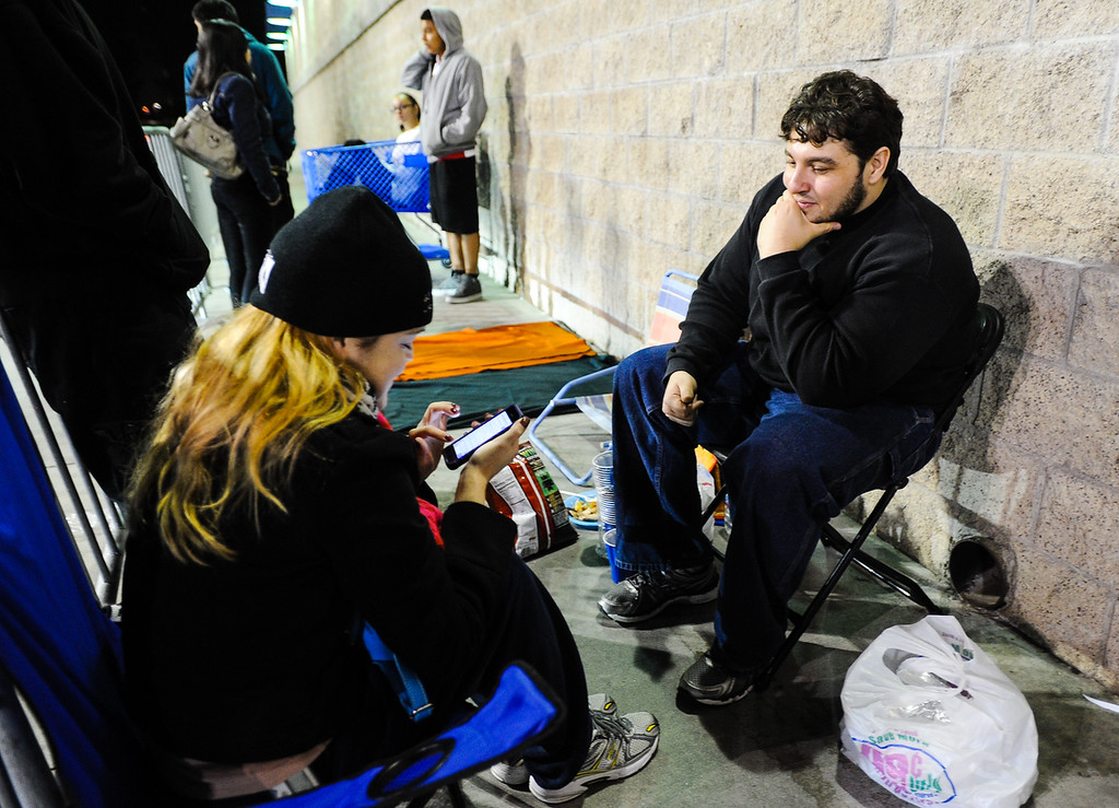 """. Highland resident Paul Andrade, right, and his friend Christina Carney, of Pomona, are the first shoppers to wait in line outside Best Buy for the store\'s \""""Midnight Mystery Doorbuster\"""" sales event on Thanksgiving in San Bernardino on Thursday, Nov. 28, 2013. Many retail stores pushed the boundary the Black Friday tradition this year with offering Black Friday deals on Thanksgiving day. (Photo by Rachel Luna / San Bernardino Sun)"""