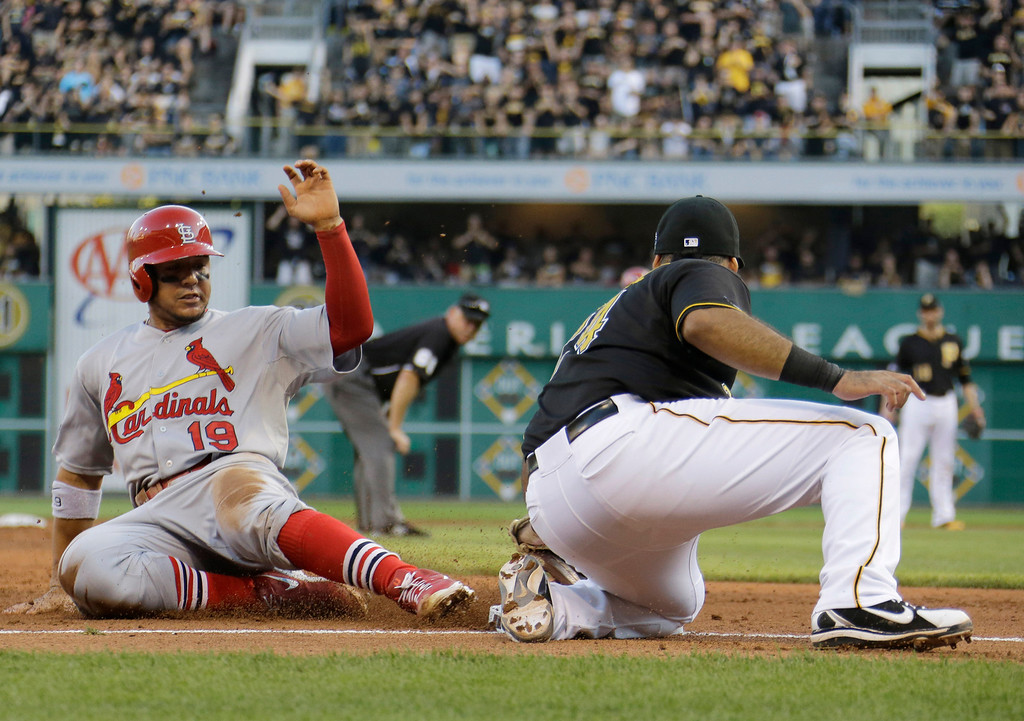 . St. Louis Cardinals\' Jon Jay (19) safely steals third base on the front end of a double-steal as Pittsburgh Pirates third baseman Pedro Alvarez, right, applies a late tag in the fifth inning of of Game 3 of a National League division baseball series on Sunday, Oct. 6, 2013, in Pittsburgh. (AP Photo/Gene J. Puskar)