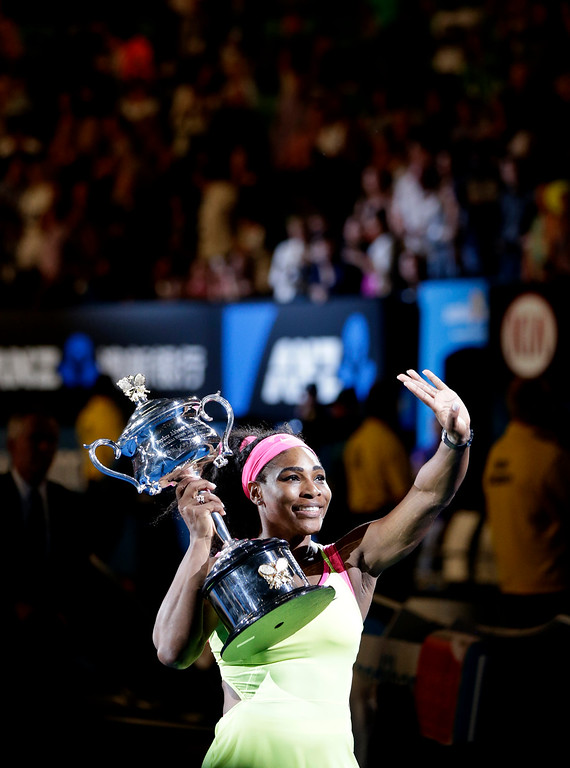 . Serena Williams of the U.S., holding the trophy, waves  after defeating Maria Sharapova of Russia in the women\'s singles final at the Australian Open tennis championship in Melbourne, Australia, Saturday, Jan. 31, 2015. (AP Photo/Vincent Thian)