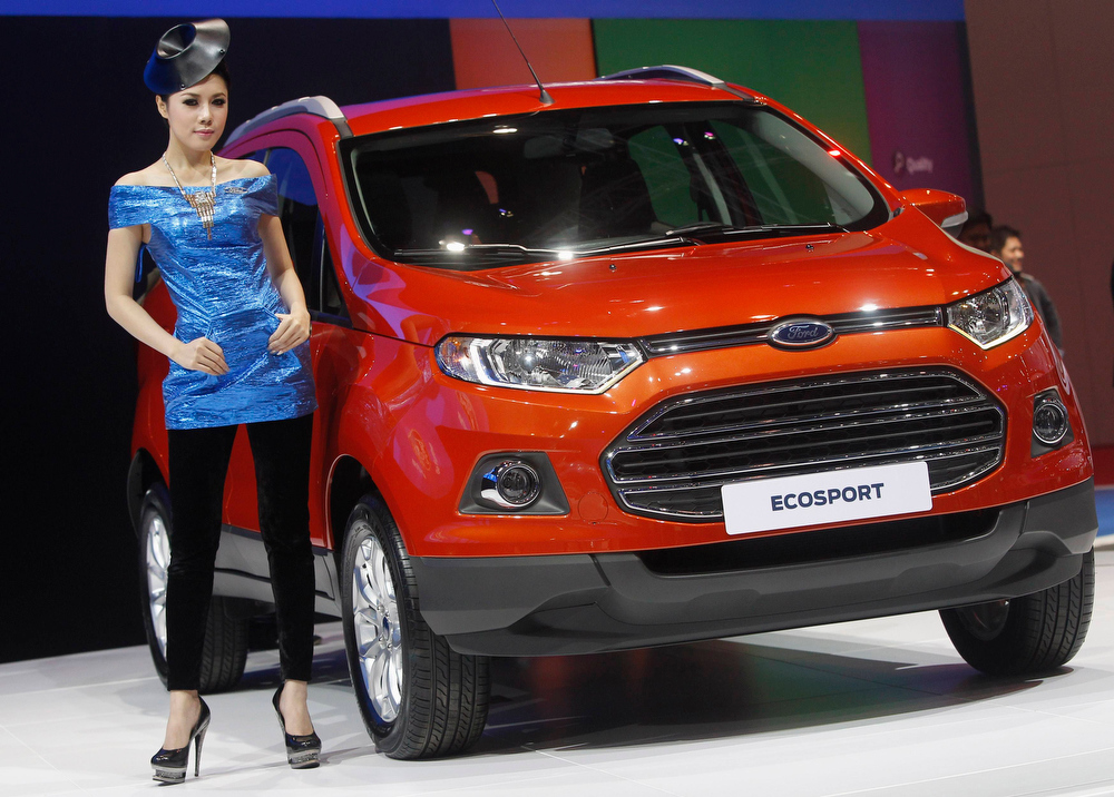 . A model poses beside a Ford Ecosport during a media presentation of the 34th Bangkok International Motor Show in Bangkok March 26, 2013. The Bangkok International Motor Show will be held from March 27 to April 7. REUTERS/Chaiwat Subprasom