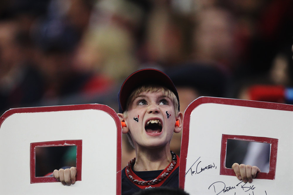 Description of . A Houston Texans' J.J. Watt fan cheers during the first quarter of an NFL wild card playoff football game against the Cincinnati Bengals Saturday, Jan. 5, 2013, in Houston. (AP Photo/Patric Schneider)