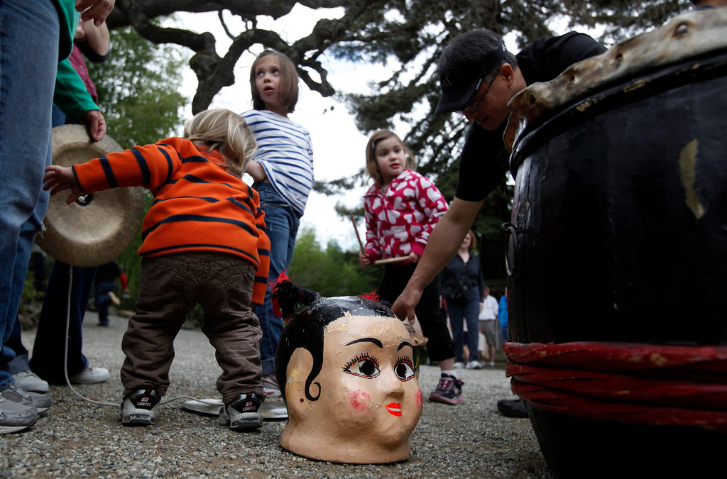 """. Young visitors mingle among the props brought by the Asian Cultural Dance Troupe to Hakone Estate and Gardens where a Lunar New Year of the Snake festival was hosted with a \""""Chinese Village Fair\"""" on Sunday afternoon, March 3, 2013 in Saratoga, Calif. (Karl Mondon/Staff)"""