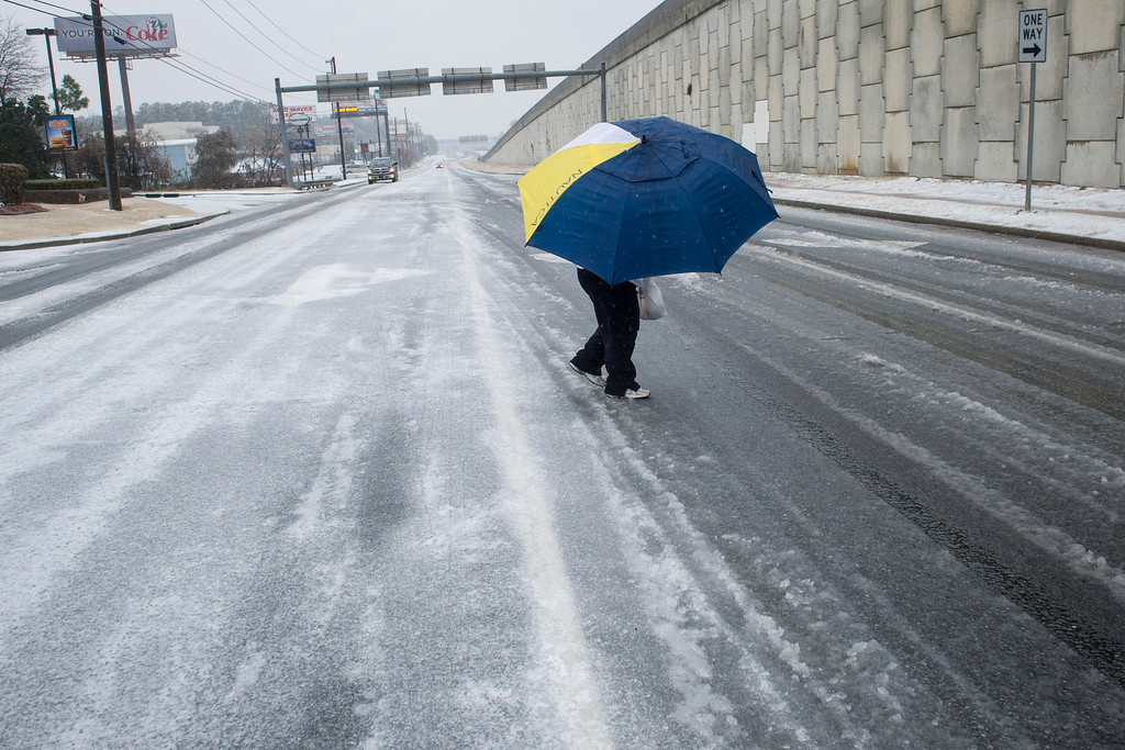 """. A woman uses an umbrella to shield herself from sleet while crossing an icy street during a winter storm on Wednesday, Feb. 12, 2014, in Doraville, Ga.  An ice storm gripped the winter-weary South on Wednesday and forecasters warned the worst of the potentially \""""catastrophic\"""" storm was yet to come.  (AP Photo/John Amis)"""