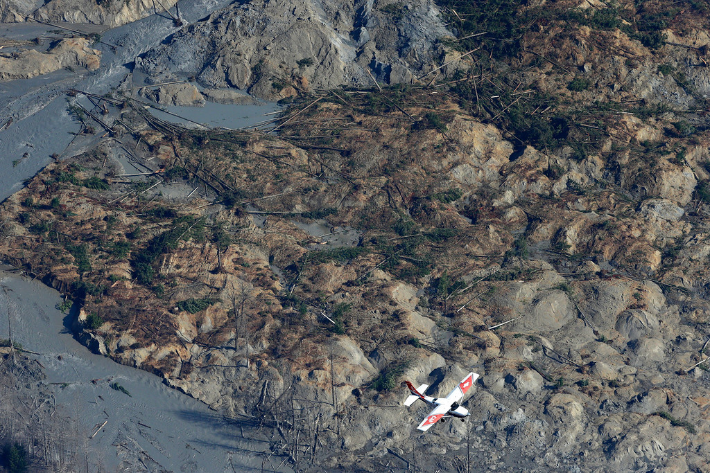. A Civil Air Patrol plane flies over the massive mudslide that killed at least eight people and left dozens missing as shown in this aerial photo, Monday, March 24, 2014, near Arlington, Wash. The search for survivors grew Monday raising fears that the death toll could climb far beyond the eight confirmed fatalities. (AP Photo/Ted S. Warren)