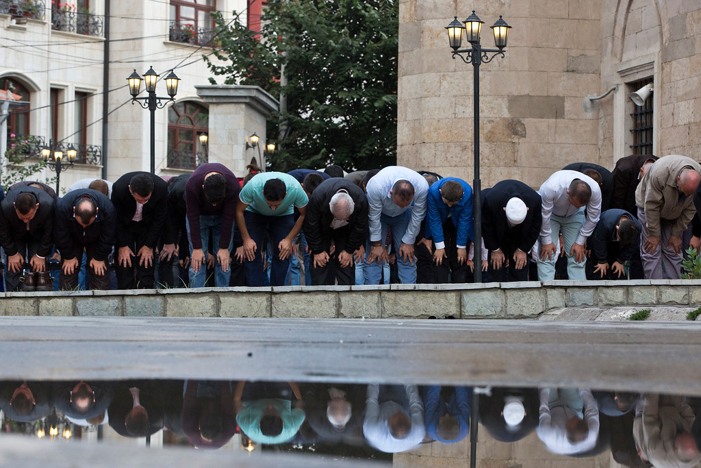 . Kosovars are reflected in water during Eid al-Adha prayers outside Sultan Mehmet Fatih mosque in capital Pristina, Monday, Sept. 12, 2016. Muslims around the world will celebrate Eid al-Adha in local language, the Festival of Sacrifice, to mark the end of the hajj pilgrimage by slaughtering sheep, goats, cows to commemorate Prophet Abraham\'s readiness to sacrifice his son on God\'s command. (AP Photo/Visar Kryeziu)