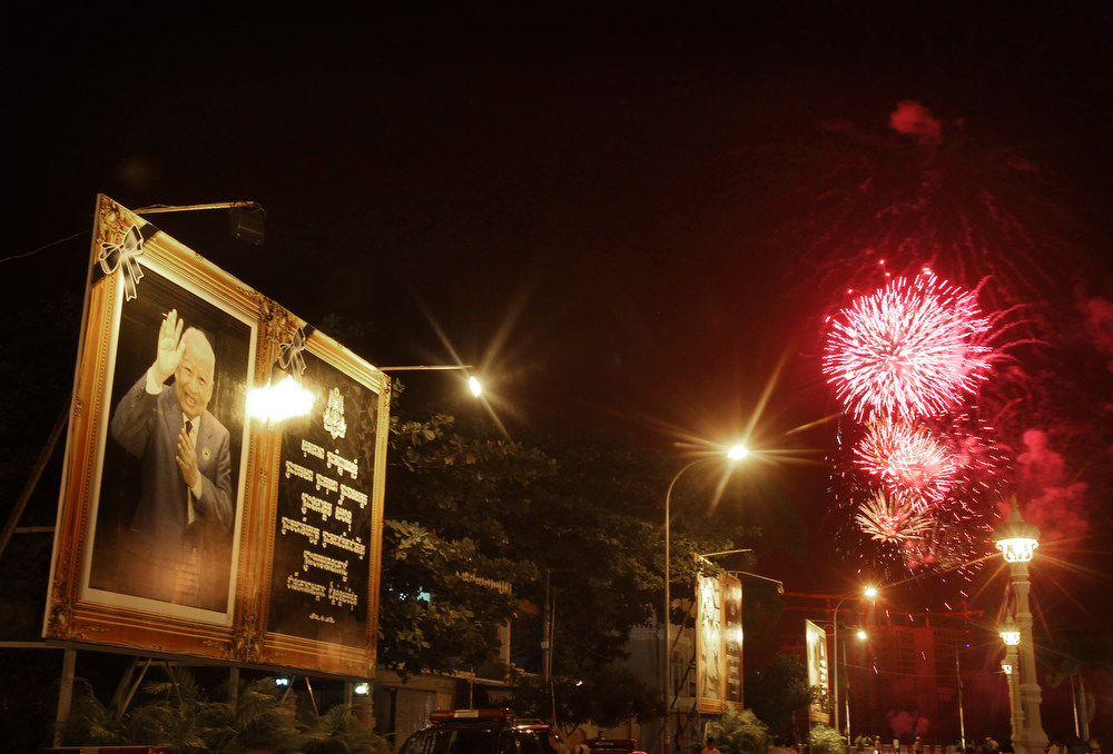 Description of . Fireworks explode next to a poster of Cambodia's former King Norodom Sihanouk as his body is cremated in Phnom Penh, Monday, Feb. 4, 2013. Hundreds of thousands of mourners gathered in Cambodia's capital Monday for the cremation of Sihanouk, the revered