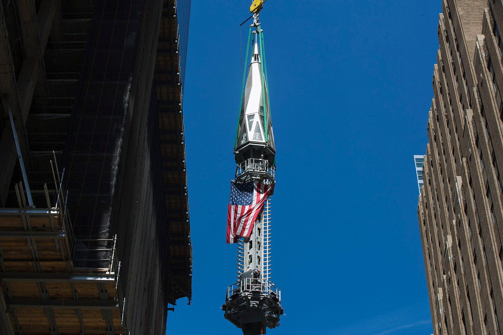 . A U.S. flag flutters in the wind as the final piece of One World Trade Center\'s spire is lifted to the top of the building in New York, May 2, 2013. REUTERS/Lucas Jackson