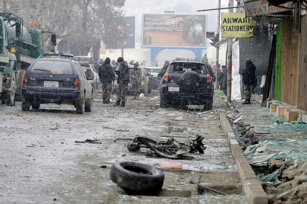 . A security official with the Afghan intelligence services, center, investigates the scene of a suicide car bomb attack in Kabul, Afghanistan, Wednesday, Jan. 16, 2013. Six militants ó one driving a car packed with explosives ó attacked the gate of the Afghan intelligence service in the capital Kabul on Wednesday, setting off a blast that could be heard throughout downtown and which sent a plume of dark smoke rising into the sky. (AP Photo/Musadeq Sadeq)