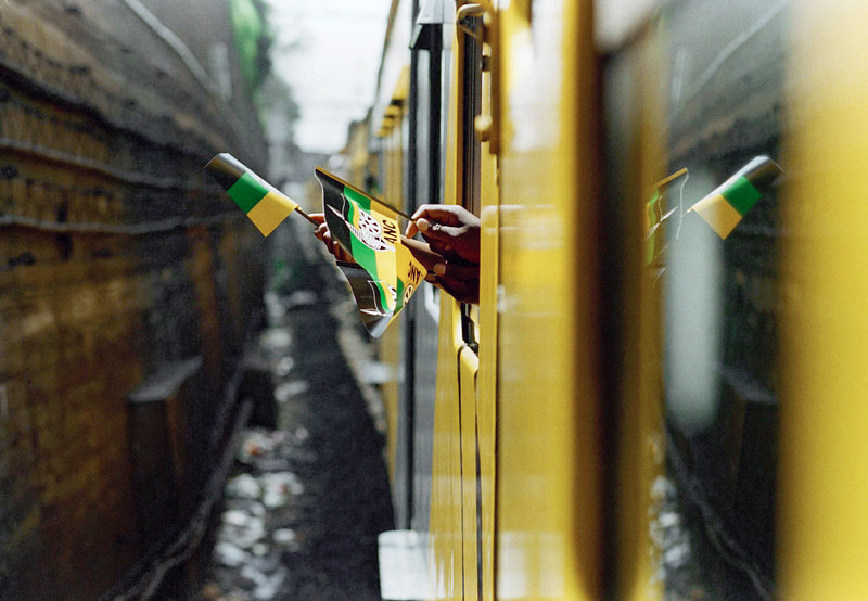 . Campaign flags from the African National Congress flutter from clenched fists out the window of a campaign train which ANC President Nelson Mandela was riding, on his way to deliver the ANC\'s election manifesto to a group of supporters in Soweto, Jan. 29, 1994.  Mandela rode the train from the center of Johannesburg to Soweto. (AP Photo/David Brauchli)