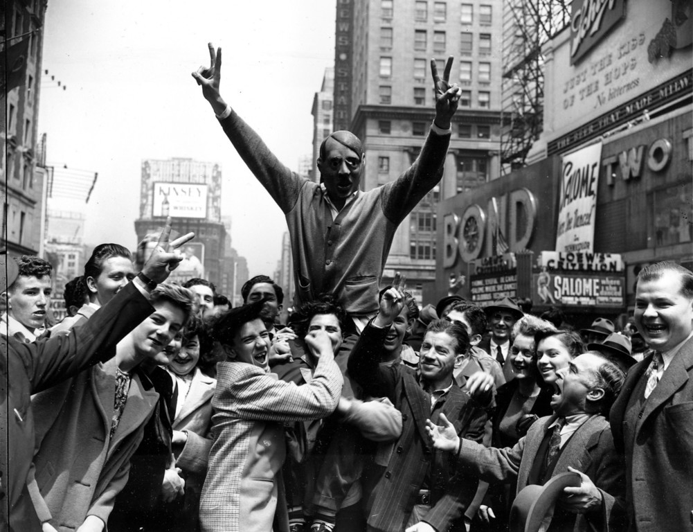 . New Yorkers gather around a youth wearing a mask of Adolf Hitler to cheer the news of the surrender of Germany in New York\'s Times Square on May 7, 1945.  (AP Photo/Harry Harris)
