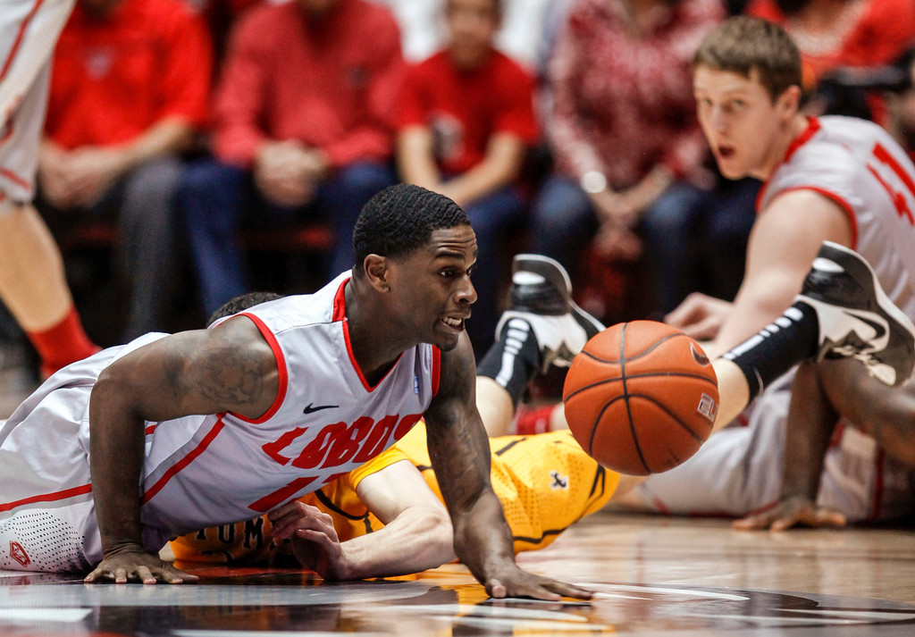 . New Mexico\'s Jamal Fenton, left, tries to recover a loose ball as teammate Cameron Bairstow watches during he first half of an NCAA college basketball game against Wyoming in Albuquerque, N.M., Saturday, March 2, 2013. (AP Photo/ Craig Fritz)