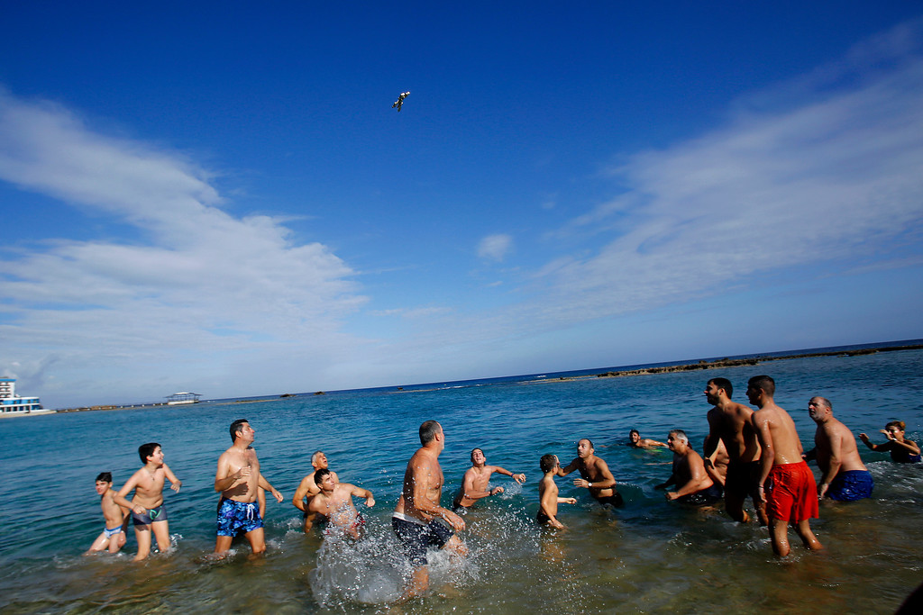 . Swimmers try to catch a cross after thrown by an Orthodox priest into the water, during an epiphany ceremony to bless the sea waters at Famagousta or Varosia beach  in the Turkish Cypriots breakaway north part of the divided island of Cyprus, Wednesday, Jan 6, 2016. More than 1,000 Orthodox Christian faithful attended the  Epiphany Day blessing of the waters in Famagusta in Cyprus�, the first time the ceremony has taken place since 1974 when the small island nation was cleaved along ethnic lines. (AP Photo/Petros Karadjias)