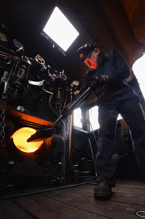 . Fireman Ken Plant stokes the boiler on the 1952 British Rail Ivatt number 46512 at Strathspey Steam Railway on August 27, 2013 in Aviemore,Scotland.   (Photo by Jeff J Mitchell/Getty Images)