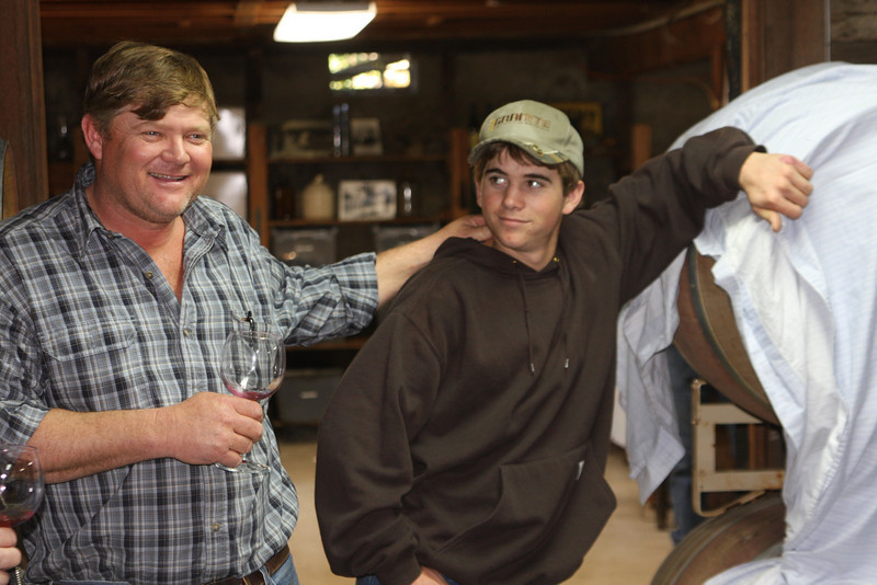 Rusty and Charlie share a laugh in the barrel room. Charlie hopes to be the sixth generation making wine under the family name.