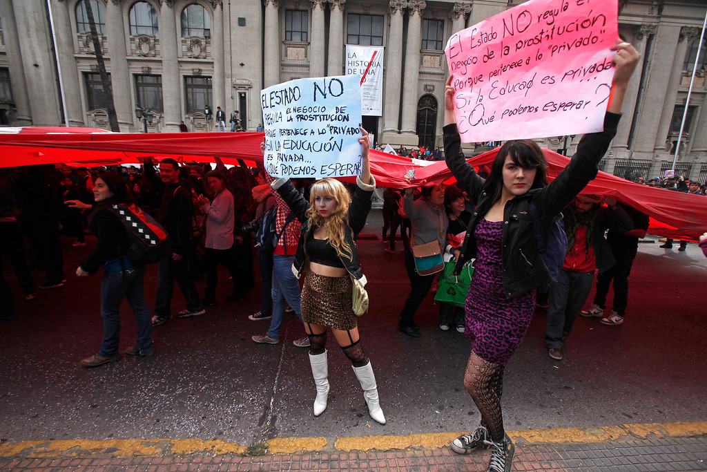 ". Two students hold up protest signs that read in Spanish; ""The state does not regulate the business of prostitution because it is a \'private business.\'  If education is a private business, what can we expect?, \"" during a student march demanding free education, in Santiago, Chile, Thursday, April. 11, 2013.  The marches began during the 2006-2010 Michelle Bachelet administration and have troubled President Sebastian Pinera even more. Pinera\'s government is focusing a chunk of the 2013 budget on financing school loans at lower rates. But students say the system still fails them, with poor public schools, expensive private universities, unprepared teachers and unaffordable loans. The(AP Photo/Luis Hidalgo)"