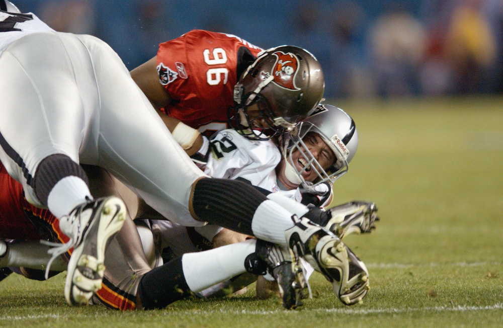 . Ellis Wyms #96 of the Tampa Bay Buccaneers sacks quarterback Rich Gannon #12 of the Oakland Raiders for a one yard loss at the Oakland 17 yardline at 4:41 of the third quarter of Super Bowl XXXVII on January 26, 2003 at Qualcomm Stadium in San Diego, California.  The sack was the fourth of five sacks by the Buccanners as they defeated the Raiders 48-21. (Photo by Doug Pensinger/Getty Images)