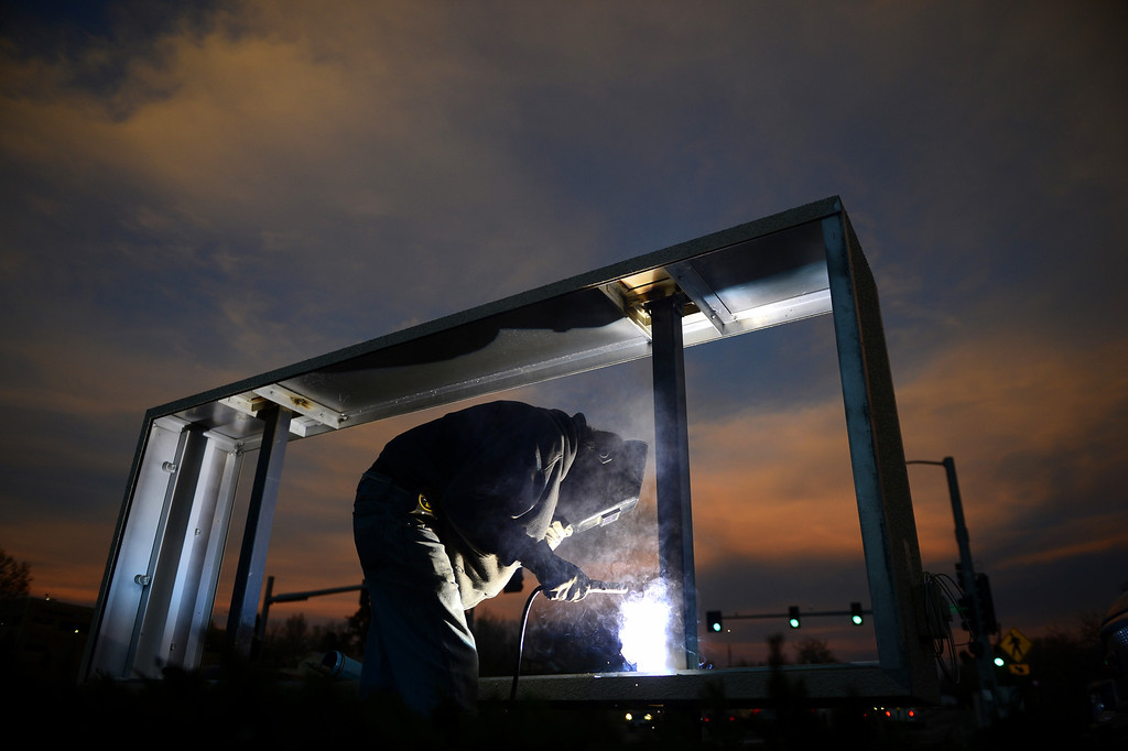. Mike Benes, of Advantage Signs, welds a frame, while installing a sign for Clarkson Medical and Dental Center at the intersection of Hamden and Clarkson on  Monday, November 5, 2012. AAron Ontiveroz/The Denver Post