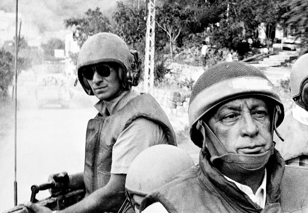 . In this June 15, 1982 file picture provided by the Israeli Defense Ministry, Israeli Defense Minister Ariel Sharon, foreground, rides an armored personnel carrier on a tour of Israeli units advancing to the outskirts of Beirut, Lebanon, during the Israeli occupation.  (AP Photo/Israeli Defense Ministry)
