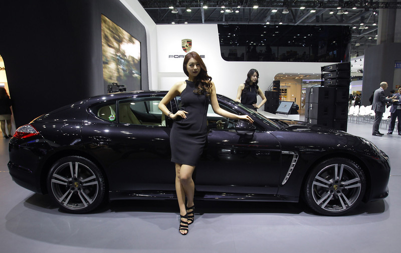 . Models pose next to a Porsche Panamera Platium Edition at the Seoul Motor Show 2013 on March 28, 2013 in Goyang, South Korea. The Seoul Motor Show 2013 will be held in March 29-April 7, featuring state-of-the-art technologies and concept cars from global automakers. The show is its ninth since the first one was held in 1995. About 384 companies from 14 countries, including auto parts manufacturers and tire makers, will set up booths to showcase trends in their respective industries, and to promote their latest products during the show.  (Photo by Chung Sung-Jun/Getty Images)