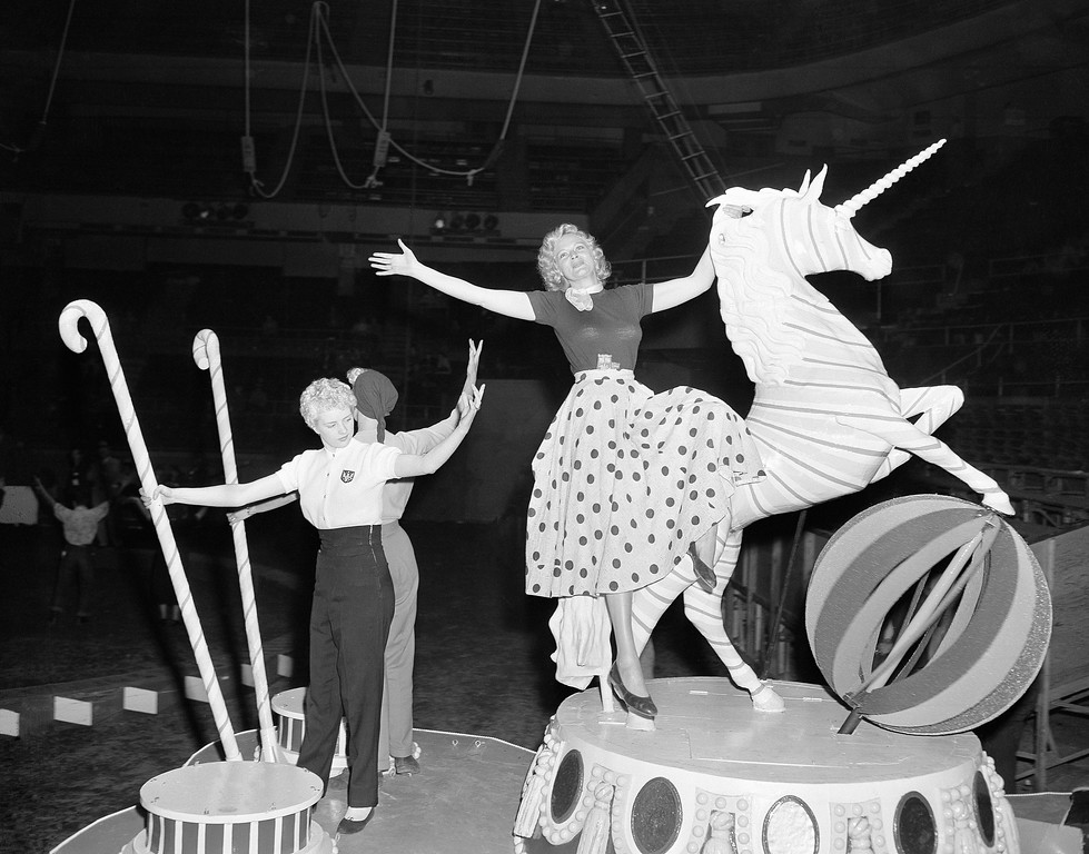 ". Getting ready for the unfolding of the symbolic ""big top\"" for the 1953 season, circus folk from Ringling Bros. and Barnum and Bailey Circus limber up at Madison Square Garden in New York, March 31, 1953, where the show makes its debut on April 1. Ann Mace, right, former Diamond Horseshoe showgirl, in street clothes, rides on the featured float, \""The Spirit of Candy Land,\"" from the \""Spectacle\"" number. (AP Photo/Ed Ford)"
