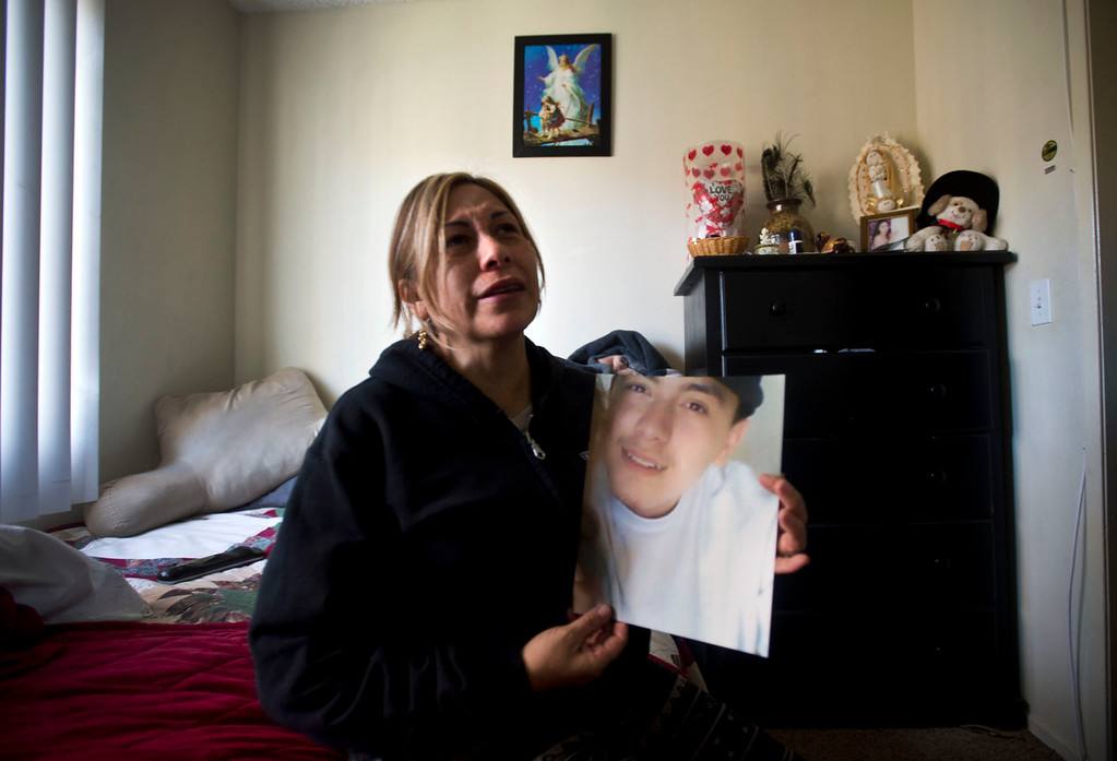 . Inside her son\'s bedroom, Carmen Avila, cries over the death of Cristopher Rossi, 16, at their Duarte apartment on Tuesday, Dec. 24, 2013. Rossi was fatally shot outside their home Monday night. (Staff photo by Watchara Phomicinda/ San Gabriel Valley Tribune)