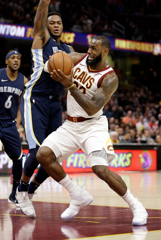 . Cleveland Cavaliers\' LeBron James, right, drives past Memphis Grizzlies\' Jarell Martin in the first half of an NBA basketball game, Saturday, Dec. 2, 2017, in Cleveland. (AP Photo/Tony Dejak)