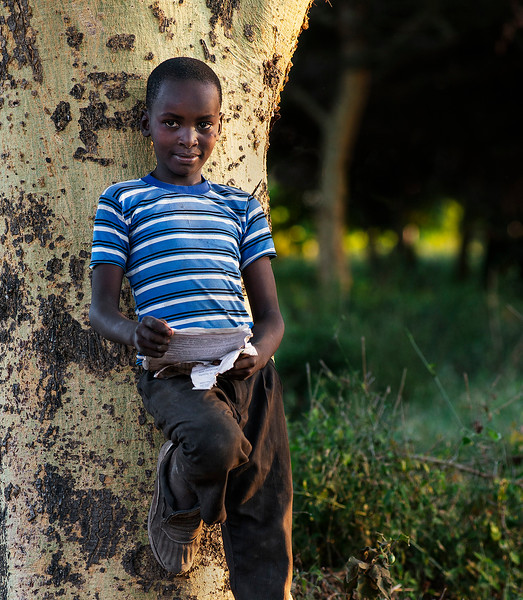 Portrait of a little boy doing his homework under a tree.  Tanzania, 2019