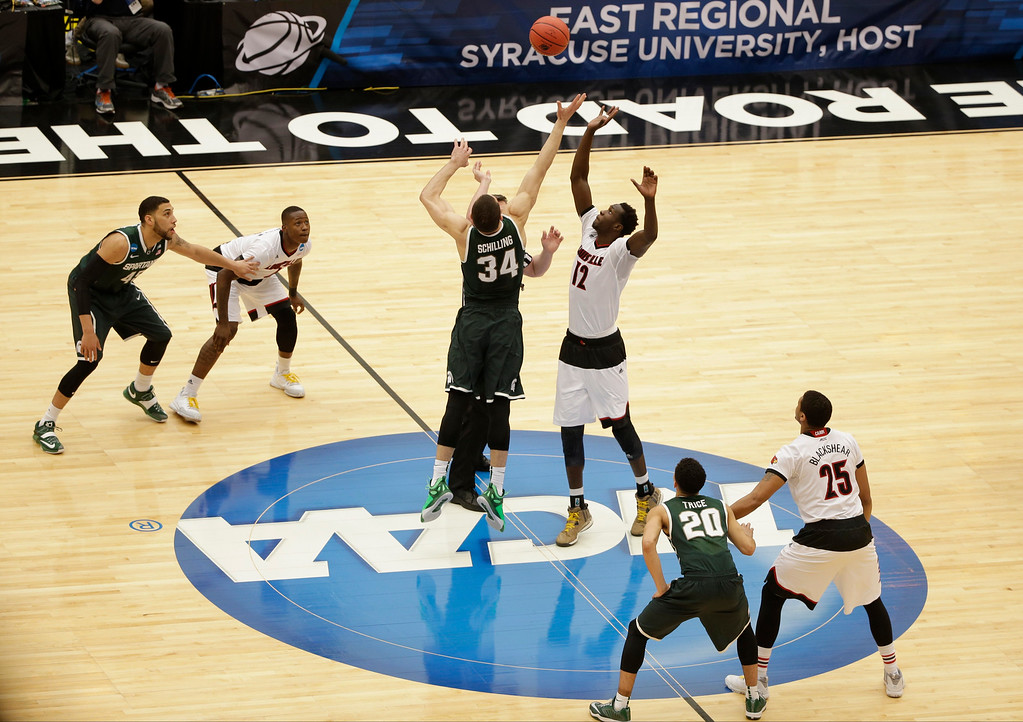 . Michigan State\'s Gavin Schilling (34) and Louisville\'s Mangok Mathiang (12), of Australia, fight for the tipoff during the first half of a regional final in the NCAA men\'s college basketball tournament Sunday, March 29, 2015, in Syracuse, N.Y. (AP Photo/Frank Franklin II)