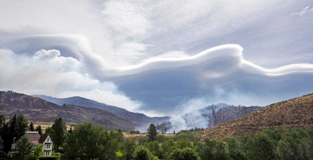 . An unusual cloud formation blends with smoke from a wildfire Saturday morning in the Methow Valley, July 19, 2014, in Winthrop, Wash. A wind-driven, lightning-caused wildfire racing through rural north-central Washington destroyed about 100 homes Thursday and Friday, leaving behind solitary brick chimneys and burned-out automobiles as it blackened hundreds of square miles in the scenic Methow Valley northeast of Seattle. (AP Photo/Elaine Thompson)