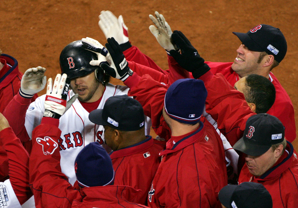 . Boston Red Sox teammates mob Mark Bellhorn, left, after his 8th -inning, two-run home run against the St. Louis Cardinals in game one of the World Series in Boston, Saturday, Oct. 23, 2004. (AP Photo/Chitose Suzuki)