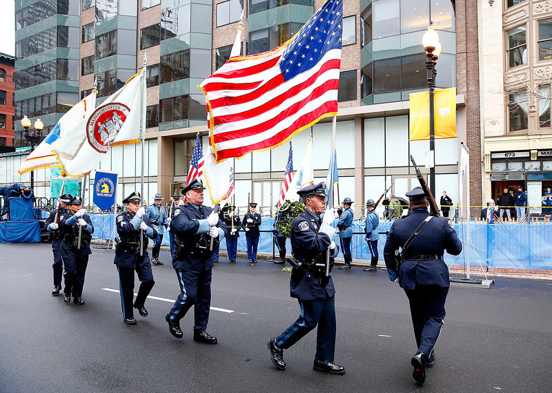 . Massachusetts state and local police and fire department members present flags during a wreath-laying ceremony commemorating the one-year anniversary of the Boston Marathon bombings on Boylston Street near the finish line on April 15, 2014 in Boston, Massachusetts. Last year, two pressure cooker bombs killed three and injured an estimated 264 others during the Boston marathon, on April 15, 2013.  (Photo by Jared Wickerham/Getty Images)