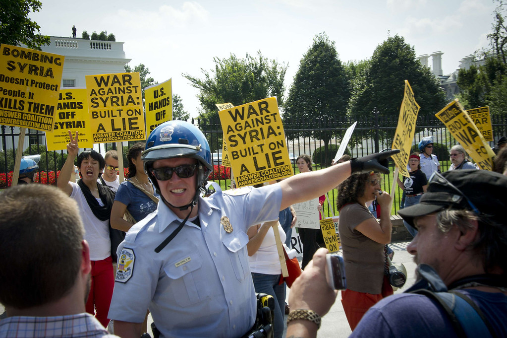 . Demonstrators are directed by a police officer in front of the White House during a rally against a possible US attack on Syria, in Washington, DC on August 31, 2013. US President Barack Obama said Saturday he will ask the US Congress to authorize military action against Syria, lifting the threat of immediate strikes on President Bashar al-Assad\'s regime. Obama said he had decided he would go ahead and launch military action on Syria, but he believed it was important for American democracy to win the support of lawmakers. MLADEN ANTONOV/AFP/Getty Images