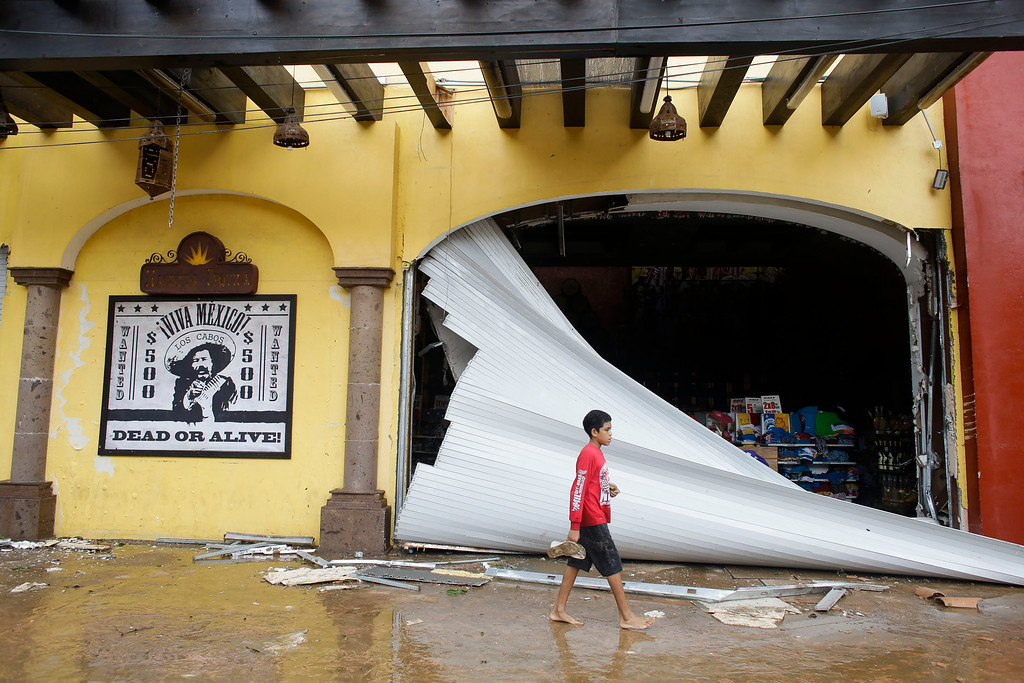 . A kid walks by a souvenir store damaged by Hurricane Odile on San Lucas\' main street, in Los Cabos, Mexico, Monday, Sept. 15, 2014.  (AP Photo/Victor R. Caivano)