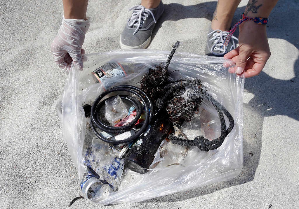 . Amanda Digiovanni, 28, of Miami, displays trash she collected on the beach while volunteering on Earth Day, Tuesday, April 22, 2014, in Miami Beach, Fla. People across the globe held events on Earth Day to celebrate the earth\'s environment and spread awareness on how to conserve its natural resources. (AP Photo/Lynne Sladky)