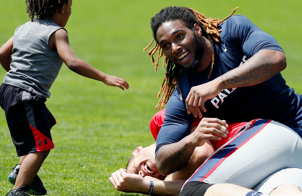 . New England Patriots running back Brandon Bolden, top, looks to his son Brycen, 3, while joking with quarterback Ryan Mallett following NFL football training camp in Foxborough, Mass., Saturday, July 26, 2014. (AP Photo)