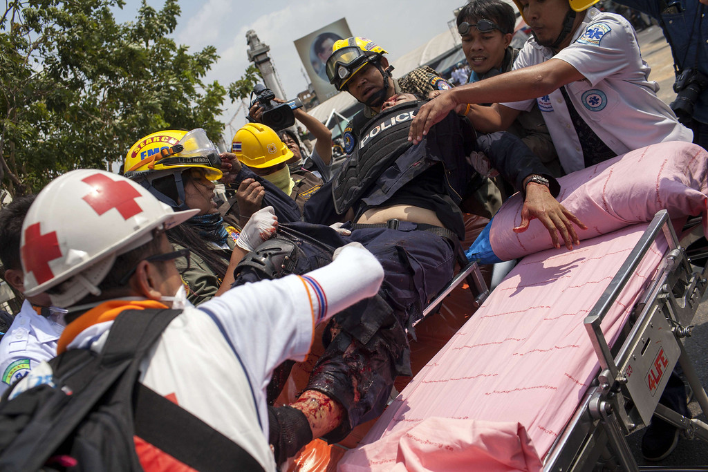 . A police officer (C) injured by a grenade thrown by anti-government protesters during a failed attempt to retake the Phan Fah Bridge is assisted by medical officers in Bangkok on February 18, 2014.  AFP PHOTO / KC Ortiz/AFP/Getty Images