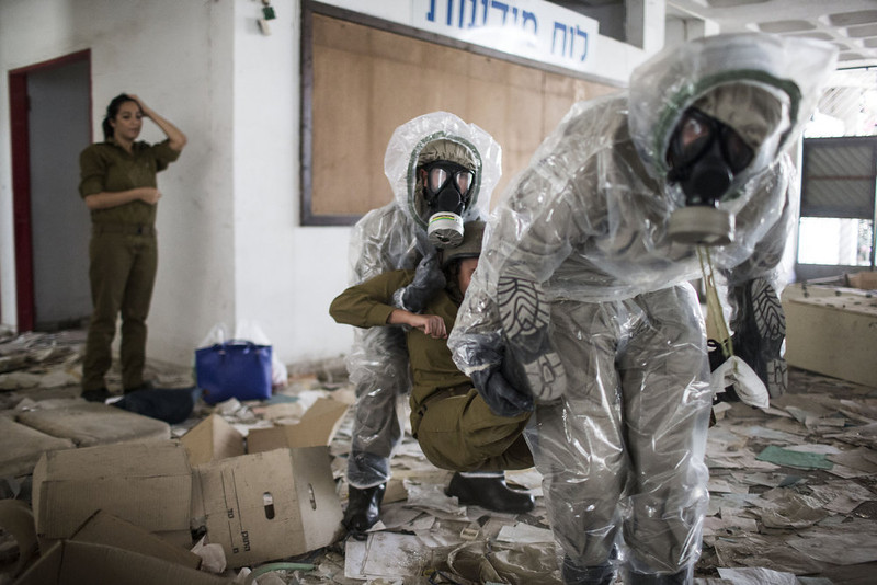 """. Soldiers of the Israeli home front brigade practice a chemical attack over a building with multiple casualties during the Home Front drill \""""Turning Point 7\"""" on May 28, 2013 in Azur, Israel. The nationwide exercise tests the civilian population\'s response to a possible massive rocket attack from three fronts. (Photo by Ilia Yefimovich/Getty Images)"""